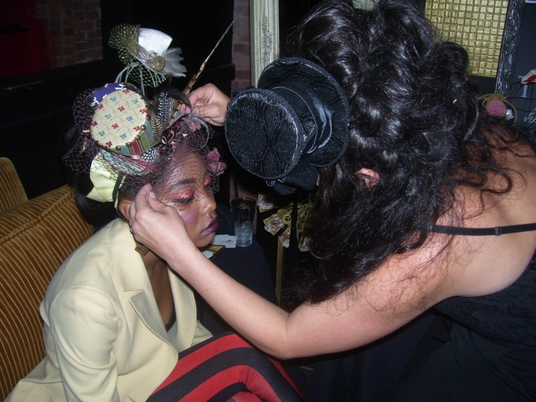 Jasika fixing one of her lovely top hats on a model (Photo by Paulette W.).